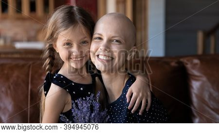 Cheerful Mom Having Cancer Posing For Portrait Cuddling Small Daughter