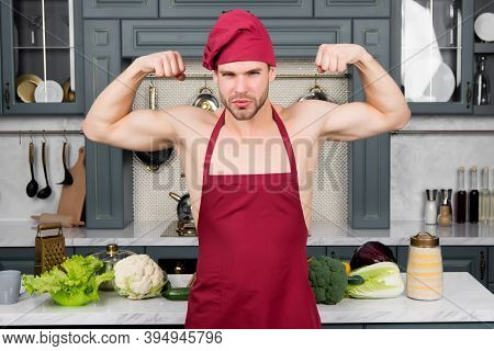 Man Chef In Red Hat, Apron On Sexy Torso Show Biceps, Triceps In Kitchen. Energy, Power Concept. Fit