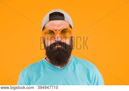 Pretend To Be Serious. Bearded Man In Sunglasses Orange Background. Hipster Wear Party Sunglasses. P