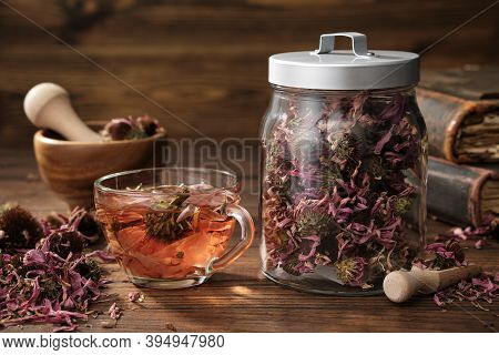 Cup Of Healthy Echinacea Tea, Glass Jar Of Dry Coneflower Herbs, Wooden Mortar And Old Books On Tabl