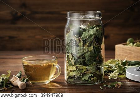 Cup Of Healthy Tea With Linden Tree Flowers, Jar Of Dry Flowers And Leaves Of Lime Or Tilia Cordata