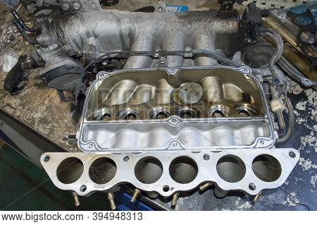 The Removed Intake Manifold Of A V6 Petrol Car Engine With Broken Air Dampers Lies On The Desktop