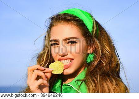 Smiling Woman Eat Potato Chips. Young Woman Biting Piece Of Potato Chips With Teeth. Tasty Delicious