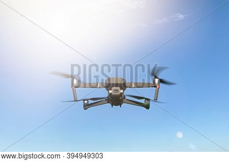 Drone hovering against blue sky and sunshine background, with light flares. Front view with space for text.