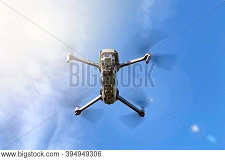 Drone hovering against blue sky and sunshine background, with light flares. Underneath view with space for text.
