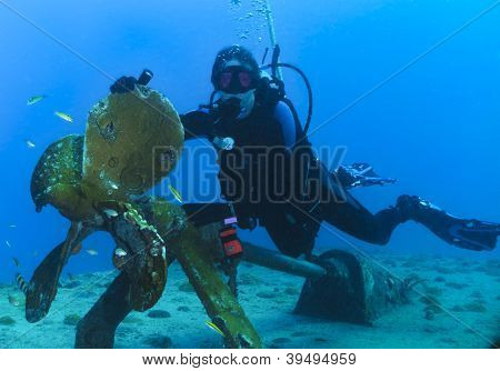 Woman scuba diver underwater on coral reef