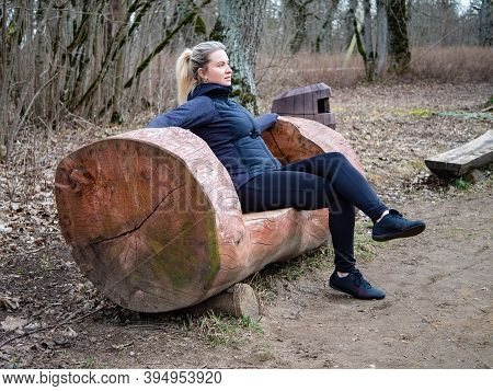 A Young Blonde Woman Is Sitting On A Wooden Bench. A Girl In Dark Blue Sportswear Is Resting In The