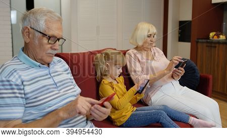 Senior Couple Grandparents With Child Girl Granddaughter Spending Time Home Together, Sitting On Sof