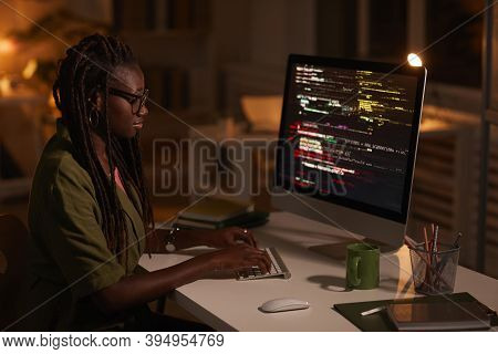 Side View Portrait Of Contemporary African-american Woman Writing Code And Looking At Computer Scree