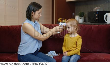 Mother Measures Temperature With Contactless Digital Thermometer Of Her Little Sick Daughter Child G