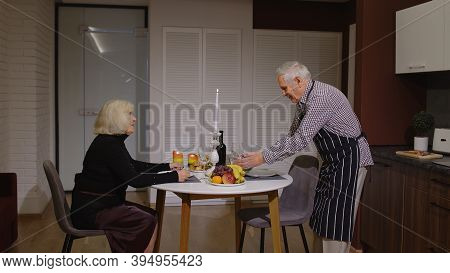 Old Elderly Man Cooking For His Wife A Romantic Supper With Wine And Candles. Senior Couple In Love,