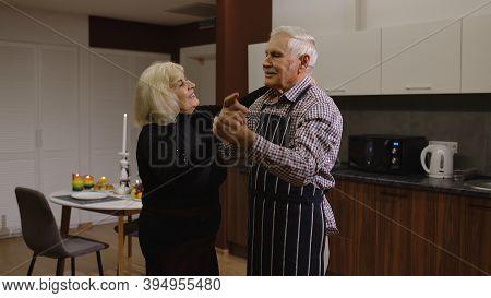 Happy Senior Couple In Love Dancing. Romantic Evening Supper With Wine And Candles, Celebrating Anni