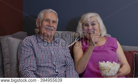 Happy Senior Old Couple Holding Remote Control Talking Laughing Watching Humor Tv Show Sitting On So