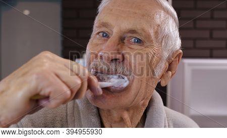 Attractive Old Senior Man Grandfather In Bathrobe Brushing Teeth Looking Into Mirror. Handsome Elder