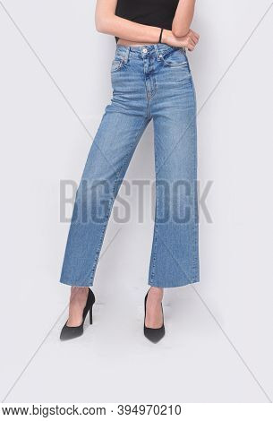 Young woman in black shirt with blue jeans and black high heels shoes posing in studio