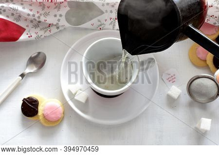Tea Ceremony/ Pouring Hot Tea Into The Cup Whit Tea Biscuits And Cookies At White Wooden Background/