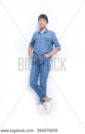 Fashion Full length young woman in jeans shirt and blue jeans hands pockets isolated on white background