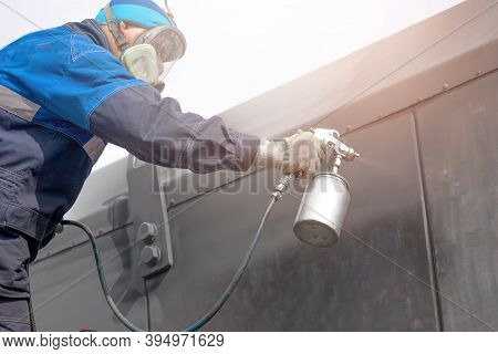 Industrial Work. Priming Of Metal Products From The Compressor Gun. A Worker In Overalls And A Prote