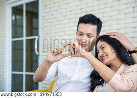 Happy Young Loving Couple Talking To Their Real Estate Agent With Smile Looking At House , Planning