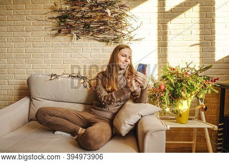 Full Size Photo Of Positive Cheerful Brown Hair Girl Sit On Sofa And Use Cellphone, Enjoy Christmas