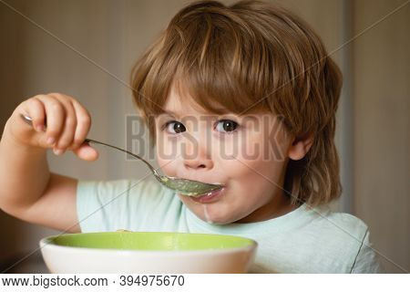 Cute Child Eating Breakfast At Home. Parenthood. Baby Eating. Young Kid Sitting On The Table Eating