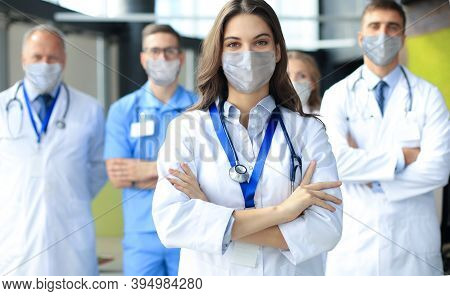 Female Doctor In Medical Mask With Group Of Happy Successful Colleagues Also In Preventive Masks.