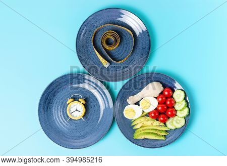 Plates With Food, Alarm Clock And Measuring Tape, Intermittent Fasting Concept.