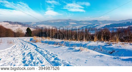 Winter Countryside On A Sunny Day. Forest On Snow Covered Hills. Mountain Ridge In The Distance Bene