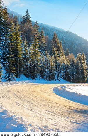 Snow Covered Road Through Forest In Mountains. Beautiful Winter Scenery At Sunrise. Spruce Trees Alo