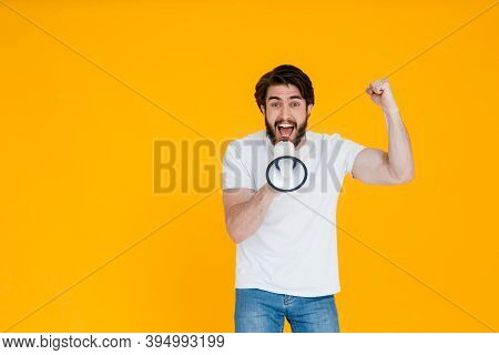 Fun Fan Young Man In A White T-shirt Posing Isolated On Yellow Orange Background, Studio Portrait. P