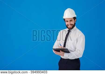 A Young Bearded Male Construction Worker In A White Shirt And Construction Helmet On A Blue Backgrou