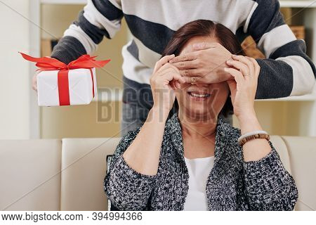 Son Covering Eyes Of His Mother From Beind And Giving Her Birthday Present