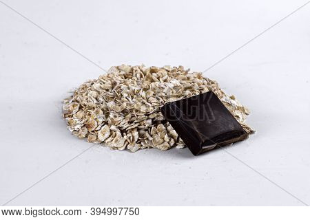 Raw Oatmeal On An Isolated On White Background. Side View Of Raw Dry Rolled Oatmeal With Chocolate