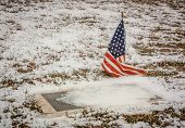 A Veteran's Grave in a Rural American Cemetery in Winter. poster
