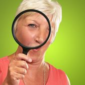 Senior Woman Looking Through A Magnifying Glass On Green Background poster