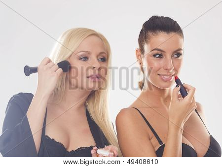 Two beautiful lingerie women doing makeup