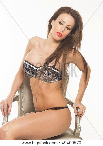 Sexy beautiful woman in lingerie in a chair on white isolated background