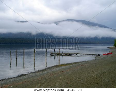 Man On Wooden Jetty On Lake Te Anau On A Cold Foggy Morning.  New Zealand