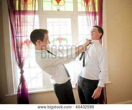 Groom and his Best Man joking and playing while they dress up and get ready for the wedding poster