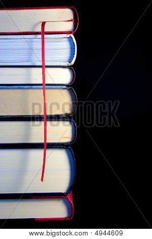 Stack Of Books In A Tower With A Red Bookmark In A Black Backgro