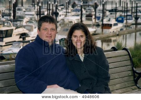 A Happy Couple Sitting On A Bench In Front Of A Marina