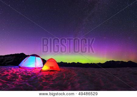 Aurora Borealis And Tents On Snow Mountain
