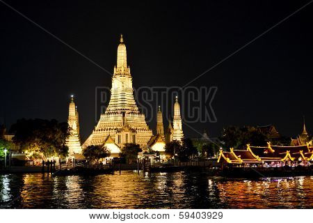 """Wat Arun or """"Temple of Dawn"""" is a Buddhist temple (wat) in Bangkok Thailand. This is a view of Wat Arun across Chao Phraya River at night. poster"""