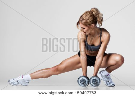 Smiling athletic woman pumping up muscles with dumbbells and stretching legs poster