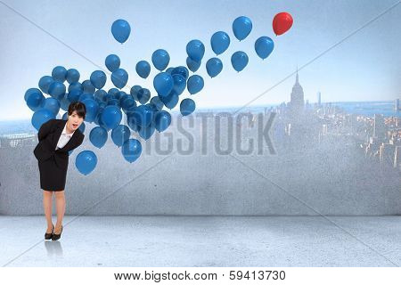 Surpised businesswoman bending against many colourful balloons in room with city on wall