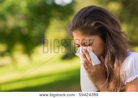 Close-up of a young woman blowing nose with tissue paper at the park