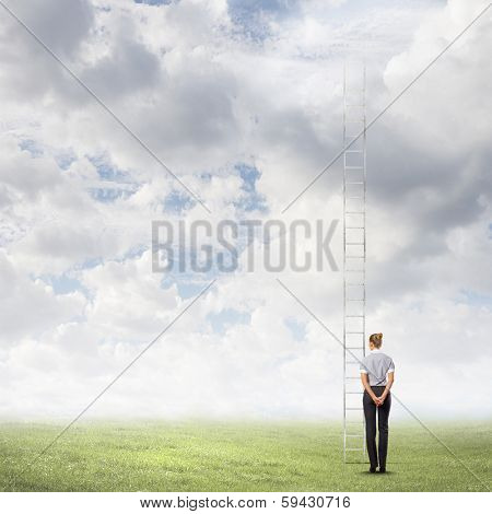 Businesswoman standing with back near long ladder to sky