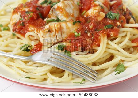 Fresh fish in arrabbiata sauce, served on spaghetti and with a fork, sprinkled with a parsely garnish, closeup