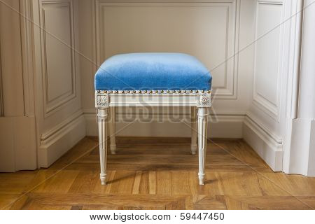 White stool with blue upholstery.