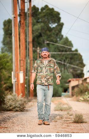 Man In Camoflauge Walking On Dirt Road